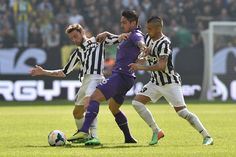 Juan Manuel Vargas (C) of ACF Fiorentina is challenged by Claudio Marchisio (L) and Arturo Vidal of Juventus during the Serie A match betwee...