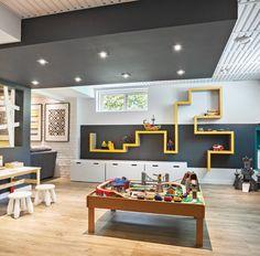 Au mur, un meuble audio fait sur mesure permet d'intégrer la large télé et le système de cinéma-maison de façon harmonieuse. Plus haut, un plafond tendu noir lustré reflète la pièce, donnant une impression de hauteur.