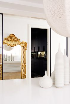 Gold framed mirror in dining space with modern vases and chandelier