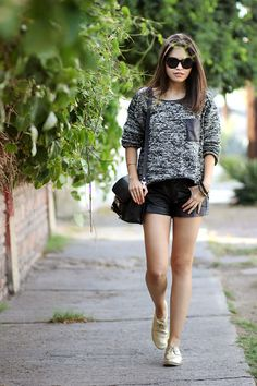 Shop this look for $88:  http://lookastic.com/women/looks/black-shorts-and-black-crossbody-bag-and-gold-low-top-sneakers-and-charcoal-crew-neck-sweater/2383  — Black Leather Shorts  — Black Leather Crossbody Bag  — Gold Leather Low Top Sneakers  — Charcoal Crew-neck Sweater