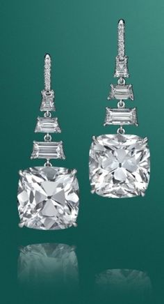 A pair of impressive 10.82 and 10.42 carats diamond ear pendants,  Each suspending a cushion-cut diamond, weighing approximately 10.82 and 10.42 carats, from a graduated trapeze-cut diamond line, to the circular-cut diamond French wire, mounted in platinum.