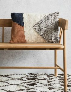geometric pillow. minimalist wooden bench. moroccan rug.