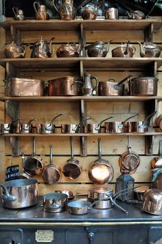OLD KITCHEN. Collection of copper pots and pans above the stove