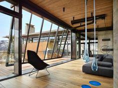 canapé gris, suspensions en verre bleu et système de fenêtres panoramiques donnant sur la montagne