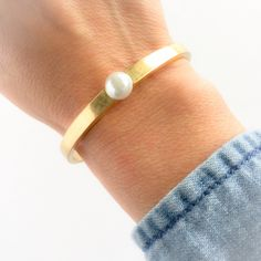 Jenny Bird Yellow Gold Blanchett Cuff. The Blanchett cuff in yellow gold comes with a nice glass pearl. Delicate and strong; a great stacking piece. Details: 14k Gold-Dipped Brass/ 8mm glass pearl. Imported (A85) Jenny Bird Jewelry Bracelets