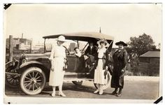 Vintage Real Photo postcard showing a group of women wearing hats. A man and boy are seated in the car. Card is black and white AZO photo with triangles pointing up and down. Postcard measures 3.5 x 5