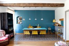 Waouuh, la totale! Mur bleu canard + jaune en touches déco + carreau de ciment/parquet Bright boho-eclectic dining space. Striking teal wall, pops of yellow & funky tiles.