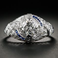 An original Art Deco engagement ring, die struck and hand finished in platinum, circa 1920s-30s, and accented with mirror image flares of calibre sapphires, sparkles front and center with a much newer, modern round brilliant-cut diamond, weighing .68 carat, for maximum sparkle.