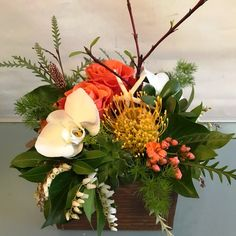 When you want to send something cheerful to a dear friend that is also unique, what better choice could you make than a Texture Box? This version features Orange Crush roses, pincushion protea, kalanchoe, phalaenpsis orchid blooms, andromeda, grevillia, succulents, ming fern, tree ivy and red twig dogwood in a wood box.