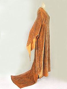 Gallenga hand-stenciled tea gown, c.1920.  The signature Gallenga style! Maria Monaci Gallenga achieved instantaneous celebrity after wearing one of her medieval-style tea gowns to a New York theatre opening in 1916.  While Gallenga's gowns varied slightly in the shape of neckline or sleeve, she remained true to her proprietary technique for stenciling on silk velvet. She used up to nine tones of silver and gold paint to achieve the ombré shadings evocative of antique fabrics. In the subtle…