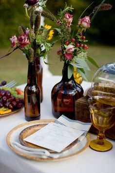 rustic red amd yellow flower and natural grass centerpieces in eclectic brown bottles | photo: www.kristynhogan.com