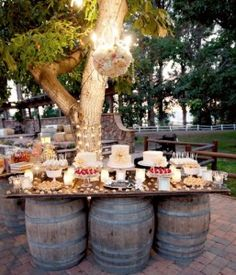 Wine barrel supported dessert table - Love this idea!