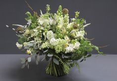 White and pale yellow bridal bouquet created from a mixture of spring flowers.