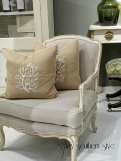 Bergere chair w/ painted finish & gray upholstery w/ beige pillows w/ embroidered white coral motif -- Savvy Southern Style