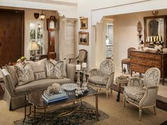 This stunning living room borrows from French country style in creating an updated traditional feel. Unique features include the concrete columns that have been faux finished to reflect saw-cut travertine. Tea-stained walls add depth to the space, yet another special addition to this well-appointed room.