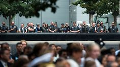 A group of motorcycle riders look over the north memorial pool during the 15th…