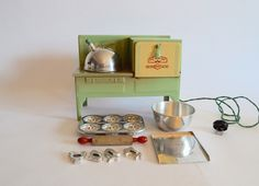 A vintage toy electric stove with oven made by Empire circa 1950's. This charming piece has a green and cream painted finish and worked when tested. The accessories include a tea kettle, muffin tin, mixing bowl, rolling pin, cookie sheet and four cookie cutters in fun animal shapes.