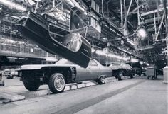 A 1971 Cadillac Calais sedan base model with no vinyl roof rolls down the assembly line, followed by a Coupe de Ville.