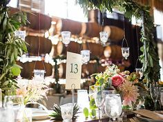 Hanging votives, garlands of greenery, simple table numbers, and wildflower arrangements. A Touch Of Grace Events.