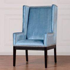 Accent the room with this ultra chic modern chair. The chair is finished in lustrous blue velvet with silver nailheads and black reclaimed oak legs.