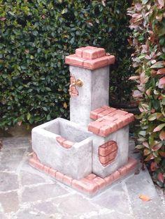 Fontanella da giardino in pietra ricostruita, con finti mattoni, modello Fonte del casale, finitura: antichizzata. Località: Marta (Viterbo).