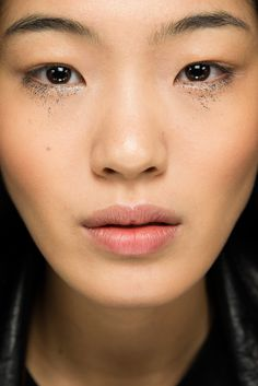 Fine black glitter sprinkled below bottom lashes on Chiharu Okunugi at Anthony Vaccarello Spring 2015 Ready–to–Wear. #SS15 #PFW