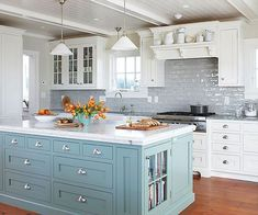 This bright and airy kitchen is full of light. Natural light paired with a white plank ceiling and cabinetry are the factors that make the space feel so open. A white marble slab creates a strong contrast with the icy-blue paint color. Metal pulls on the cabinets and drawers add shine to the room. Added sparkle comes from the dove gray backsplash tiles. Reddish-brown floors keep the room grounded and add warmth to the space.