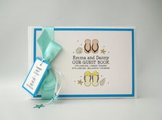 Beach Wedding Flip Flop Guest Book - A delightful illustration of a pair of female and male flip flops on a beach with beach shells and starfish, personalised with the location of the wedding venue (if marryiing abroad)