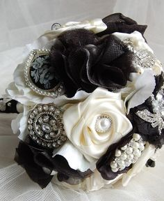 "Elegant Black & Silver Bouquet - 9.5"" diameter. Handmade satin, lace, organza and fabric flowers throughout, decorated with a selection of crystal and pearl brooches, and pearls throughout. Lace surround with satin underneath and satin trimmed handle, finished with lace, pearl pins and diamante brooch by Ruffled Ruby"
