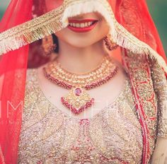 Pakistani / Indian / South Asian wedding photography | dulha and dulhan on instagram | pose for showing vibrant lip color, necklaces and details on the blouse - Bridal photo shoot