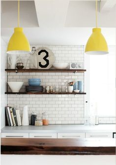 White subway tiles with grey grout and wooden shelves with yellow pendant lights.