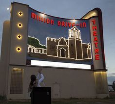 Leticia Ozuna, City Councilwoman of District 3, applauds the official lighting of the recently completed Mission Drive-In Mural at the Mission Drive-In Theatre on Feb. 12, 2013.