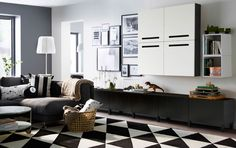 A large livingroom with black-brown low storage with drawers and black-brown wall cabinets with white doors. Shown together with a dark grey two-seat sofa with chaise longue and a black/white rug.