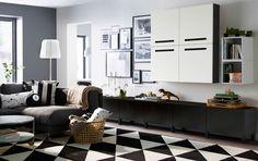 Grand séjour avec rangements bas à tiroirs brun-noir et éléments muraux brun-noir à portes blanches. Un canapé deux places avec méridienne gris foncé et un tapis noir et blanc complètent l'ensemble.