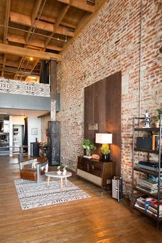 I love the use of wood to contrast the brick wall- This could be a really easy way to temporarily change the style of a room. Maybe even mount a tv off of it?