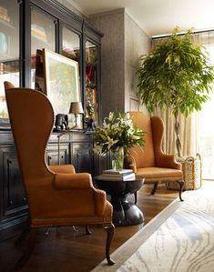 wingback chairs, grasscloth walls, black, and brass. lovely.
