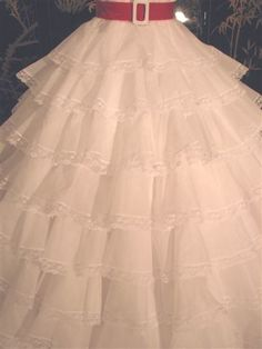This version of the gown is made in a lighter weight cotton organdy . Additionally it employs a favorite designer technique for the construction of the skirt ruffled layers. This produces a fluffier appearance with less bulk. Skirt is over 350 inches wide at hemline. taradresscuskirt.JPG (360×480)