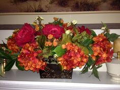 """Poppy hydrangeas and deep red roses give this fall mantle arrangement a special glow. 24"""" long and 9"""" high in a pounded metal rectangular container.  www.customsilkfloral.com"""