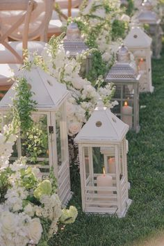 Pillar candles were housed in antique lanterns surrounded by lush arrangements of white florals and greenery. #weddingceremony #decor Photography: Kris Kan. Read More: http://www.insideweddings.com/weddings/lauren-kitt-and-nick-carter/605/