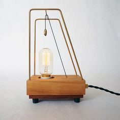 Lamp 'Pull' | Unique table lamp handcrafted made with oiled Hickory and Mahogany wood. The black pull cord over the brass frame switches the lamp on/off. A small wooden disk controls the built-in dimmer. | #lamp #tablelamp #light #retro #edison #wood #design #lighting #brass #ceramic #dimmer #deco #vintage #authentic #pullswitch #handmade #handcrafted #object #exclusive #hickory #T45 #unique