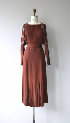 Vintage 1930s copper rayon crepe dress with squared neckline, long silver beaded dolman sleeves, beaded shoulders, bias construction, matching beaded belt and side snap closures. --- M E A S U R E M E N T S --- fits like: medium shoulder: n/a bust: 36 waist: 31 hip: 44 length: 52 brand/maker: n/a condition: excellent ✩ layaway is available for this item To ensure a good fit, please read the sizing guide: http://www.etsy.com/shop/DearGolden/policy ✩ ...