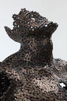 Esculturas com elos de metal.