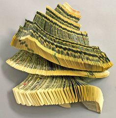 """Brooklyn book sculptor Doug Beube began altering books in 1979 by cutting, folding, gouging, piercing, and slashing. He excavates found books as if they were undiscovered archeological sites,"""" reports Art Made From Books."""