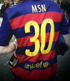 A fan wearing MSN jersey in the Camp Nou (Messi 10, Suarez 9, Neymar 11) .