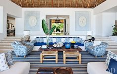 The living room sofa, with seat and back cushions of Chameleon fabric by Perennials, is flanked by custom-made chairs upholstered in Kaba Kaba linen by Bullard. Niches in the rear wall display Bali-inspired stenciling by artist Kelly Holden.