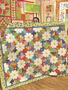 """From Strawberry Patch, this shows Amanda Murphy behind her """"Blossom"""" quilt. I love her color/fabric choices! This could be more easily done, but still pretty, using squares where the flowers are."""