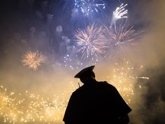 A Cincinnati police officer stands beneath a Labor Day fireworks display. The annual end-of-summer festival culminates with Rozzi's Famous Fireworks display and draws thousands to the banks of the Ohio River in downtown Cincinnati and northern Kentucky.   John Minchillo, AP