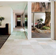 O corredor tem piso de pedras São Tomé, na mesma linguagem da área externa. Projeto do escritório Reinach Mendonça.
