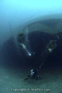 Scuba divers explore 12 inch main guns on shipwreck USS Arkansas, Bikini Atoll, Marshall Islands, Micronesia, Pacific