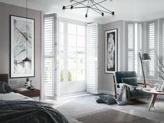 Bedroom with white full length shutters